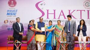 Smt Anita Sheth, Promotor,Kanidha Mahila Gruhudyog receiving her trophy by Shri Haribhai P. Chaudhary, MOS, MSME & Dr. Nirmla Sunil Wadhwani, Hon'ble Minister of State for Women & Child Development, Govt of Gujarat